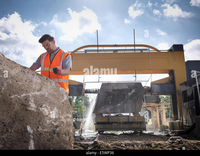 Quarry worker measuring rock in front of stone saw - Stock Image