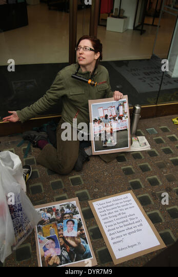 London, UK. 24th April 2014. A protester with her necked chained on the glass doors of the Oxford Street store. - Stock Image