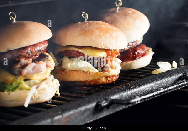 Delicious burgers with beef, tomato, cheese and lettuce. cooked on the grill assembled. heat the grill and the smoke - Stock Image