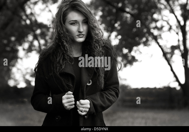 Woman in black outside in rain - Stock Image