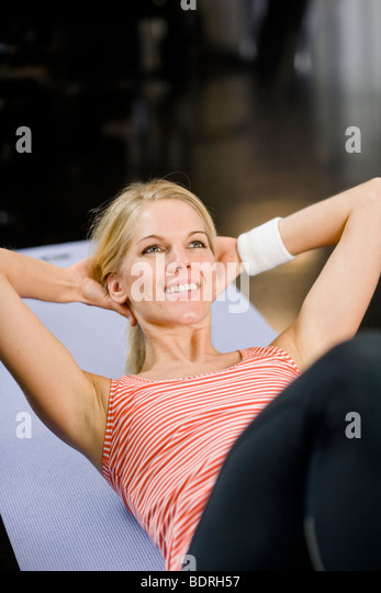 A woman doing sit-ups at a gym - Stock Image