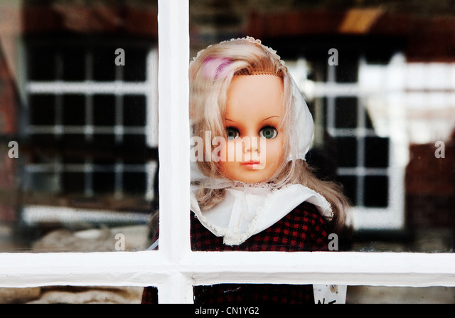 Doll looking out of window - Stock Image