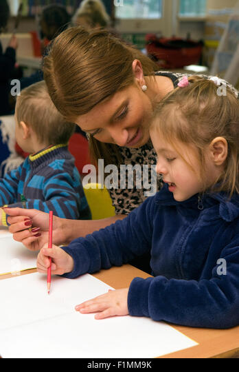 Primary school teacher assisting pupil in classroom, London, UK. - Stock Image