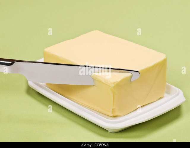 ein Stück Butter wird angeschnitten | a piece of butter is sliced - Stock Image