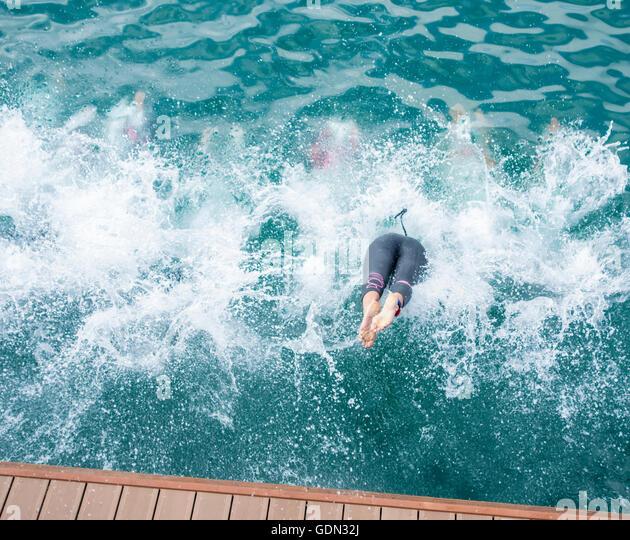 Female triathletes diving into sea at start of triathlon race. - Stock-Bilder