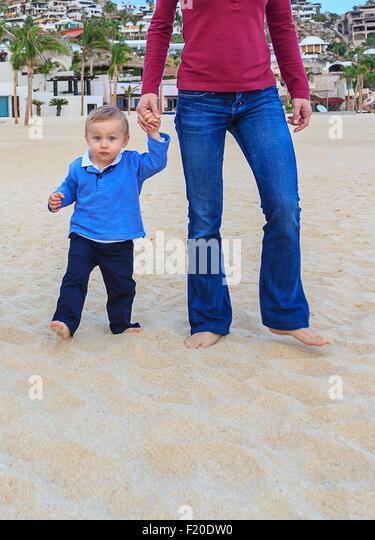 Mother and son on beach, holding hands, low section - Stock Image