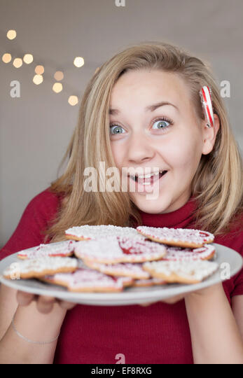 Smiling girl (14-15) holding plate of christmas cookies - Stock Image