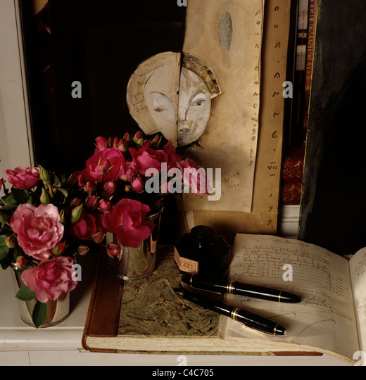 Detail of pen and ink on old fashioned book on surface with camellias - Stock Image