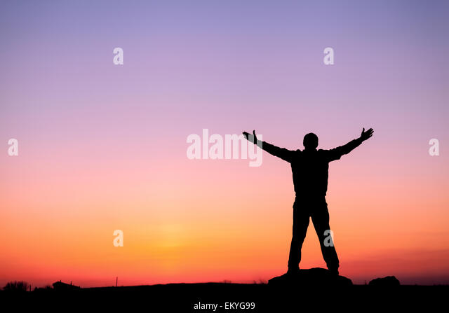 Silhouette of man with arms raised up and beautiful sky. Element of design. Summer sunset. Background - Stock-Bilder