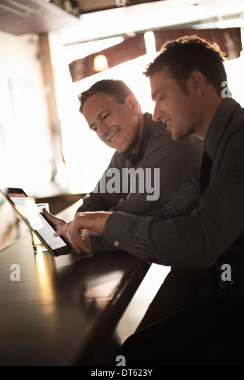 Two businessmen looking at digital at the bar - Stock Image