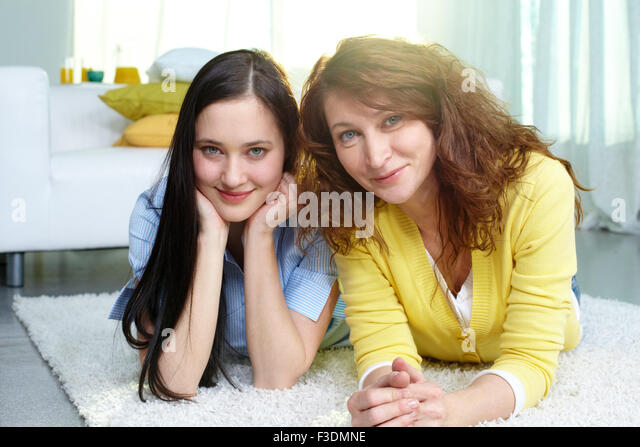 Restful mother and daughter lying on the floor at home - Stock Image