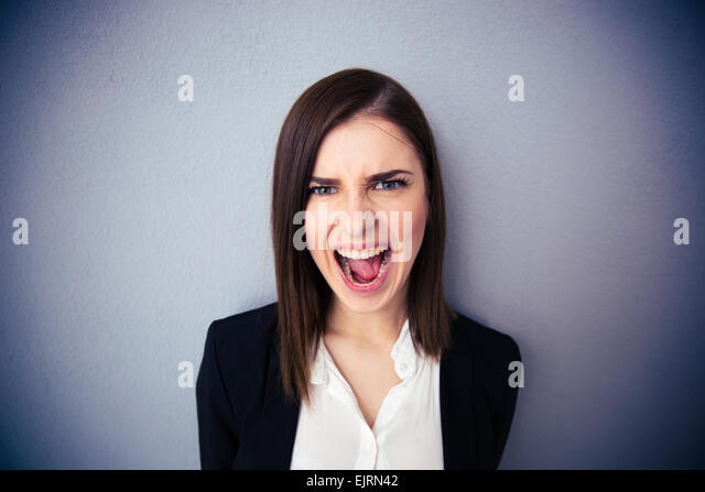 Angry businesswoman shouting over gray background. Looking at camera - Stock Image