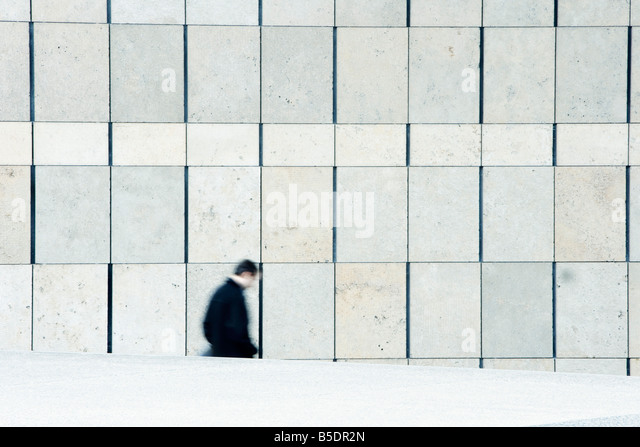 Businessman descending stairs leading down from sidewalk - Stock Image