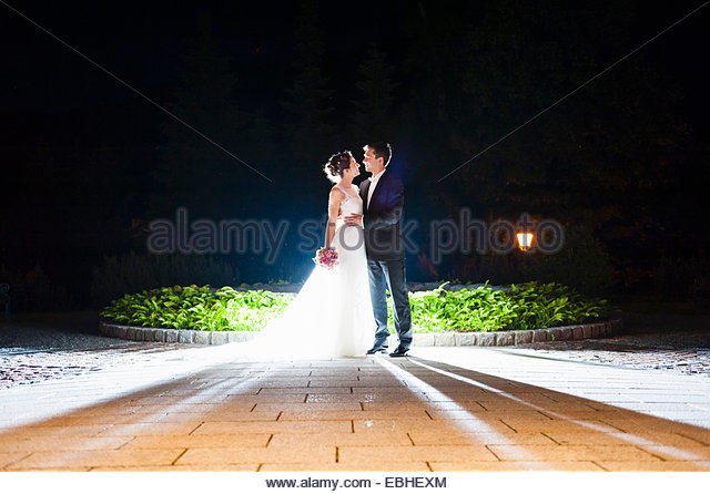 Romantic newlywed mid adult couple illuminated in garden at night - Stock-Bilder