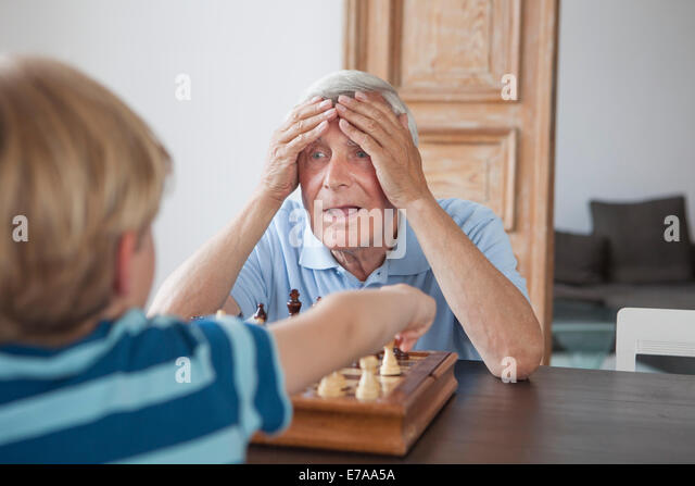 Shocked senior man with head in hands looking at grandson while playing chess at home - Stock-Bilder