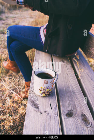 Young woman with a cup of coffee in a wooden bench - Stock Image