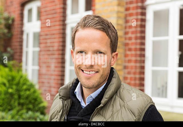 Mid adult man smiling towards camera - Stock Image