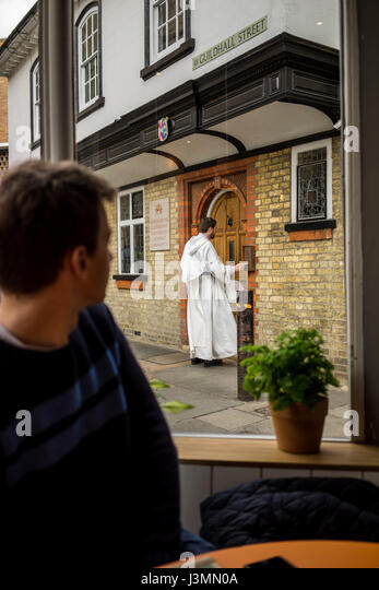A priest in robes in the University city of Cambridge in England - Stock-Bilder
