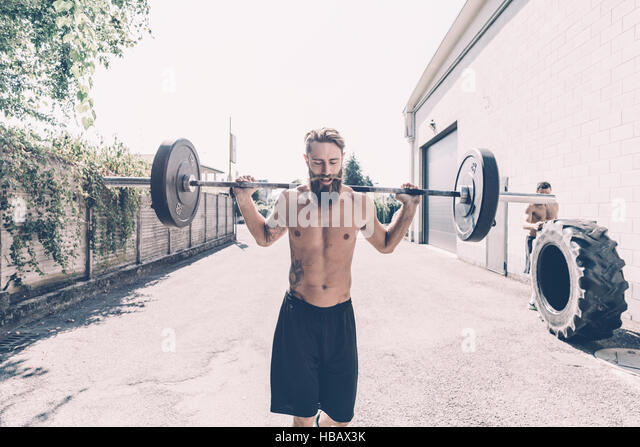 Young male cross trainer weightlifting barbell outside gym - Stock Image