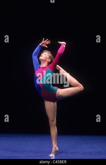 Female gymnast on the balance beam. - Stock Image