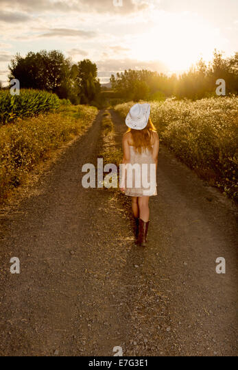 Beautiful country girl walking towards the sunset - Stock-Bilder