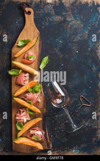 Prosciutto, cantaloupe melon and wine glass over dark plywood background - Stock Image