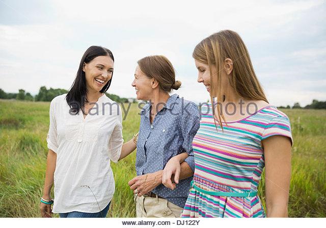 Female family members walking through field - Stock Image