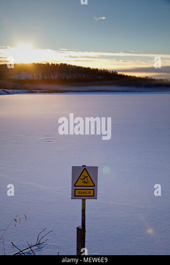 Frozen lake at dusk with a  sign warning in Swedish to walk on the thin ice. - Stock Image