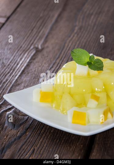 Fresh made Honeydew Jello on wooden background - Stock Image