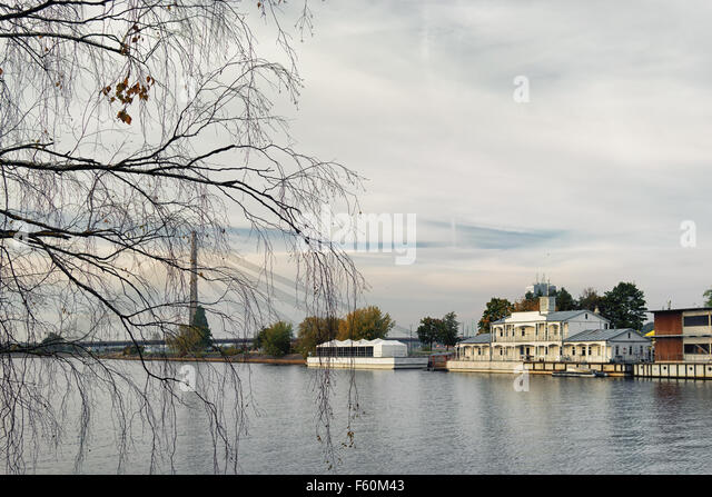 Wooden houses and barges on the River Daugava have cable-stayed bridge in Riga on background thin branches of autumn - Stock Image