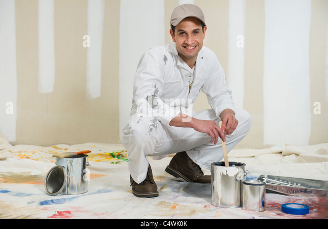 USA,New Jersey,Jersey City,house painter stirring paint - Stock Image