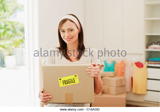 Woman carrying box with fragile sticker into new house - Stock Image