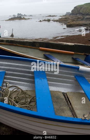 Detail of blue and white rowing boat on a Cornish beach in winter - Stock Image