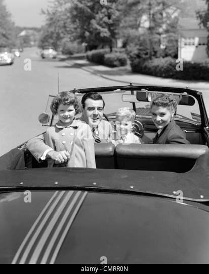 1950s PORTRAIT WELL DRESSED FAMILY MOM DAD SON DAUGHTER IN CONVERTIBLE CAR TOP DOWN LOOKING AT CAMERA OVER BACK - Stock Image