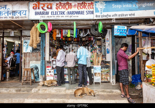 Mumbai India Asian Dharavi Shahu Nagar Road small businesses business man electric hardware store stray dog dogs - Stock Image