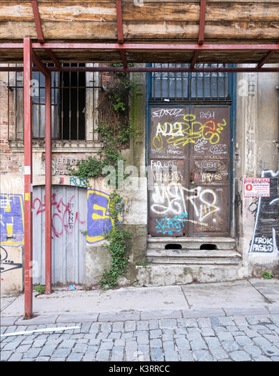 Istanbul, Turkey - April 18, 2017: Grunge abandoned metal door and windoe with random paints - Stock Image