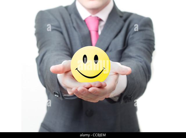 Businessman holding smiley - Stock Image
