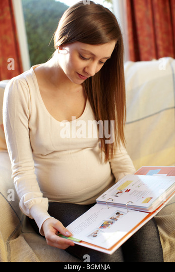 Pregnant woman reading home pregnancy book - Stock Image