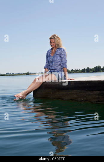 Woman relaxing on dock - Stock Image