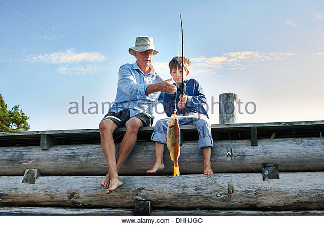 Grandfather and grandson fishing, Utvalnas, Sweden - Stock Image