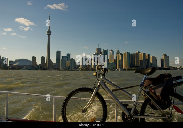 City of Toronto skyline from island ferry with bicycle in foreground. - Stock Image