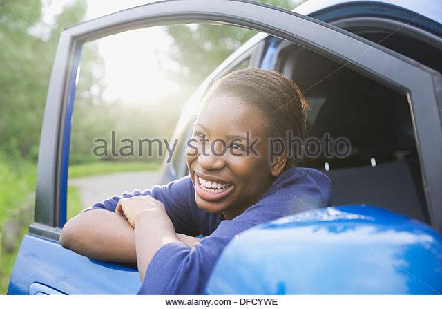Cheerful teenage girl leaning on car door - Stock Image