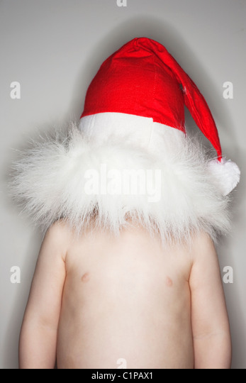 Boy wearing santa hat over head - Stock Image