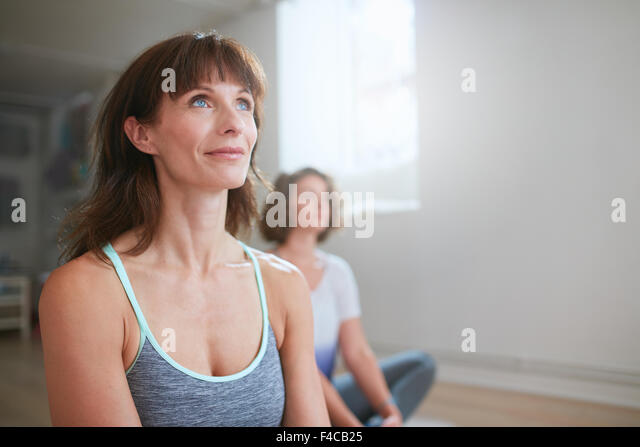 Portrait of fitness woman sitting on floor in yoga class looking away. Yoga trainer during workout  session in gym. - Stock Image