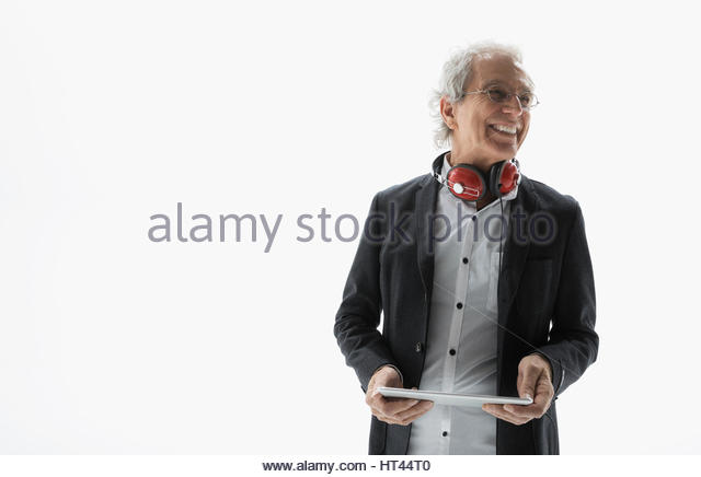 Smiling senior man with headphones using digital tablet against white background - Stock-Bilder