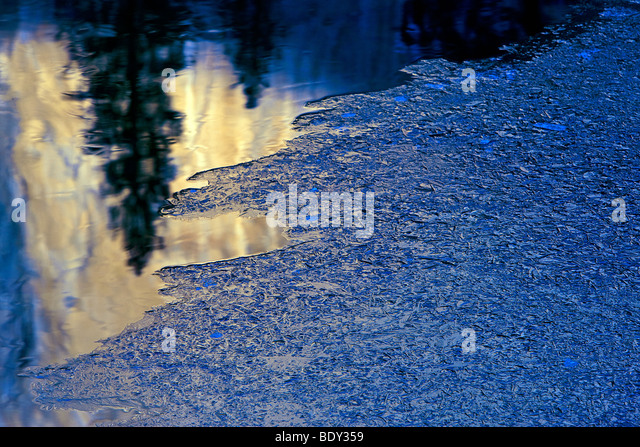 A warm reflection of El Capitan contrasts with ice in the Merced River, Yosemite National Park, California, USA. - Stock Image