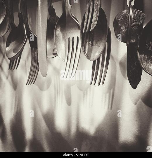 Kitchen utensils hanging on a wall - Stock Image