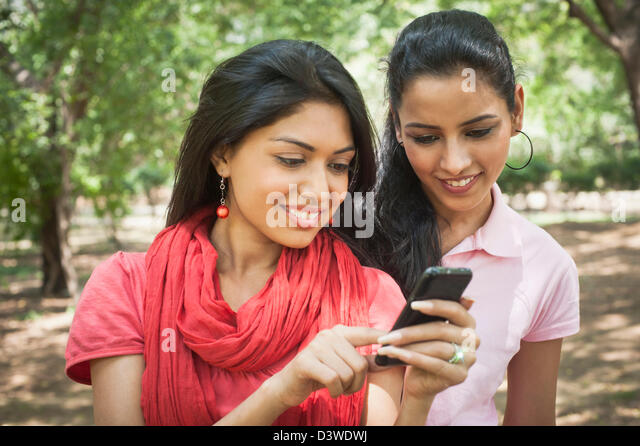 Friends text messaging on a mobile phone, Lodi Gardens, New Delhi, Delhi, India - Stock-Bilder