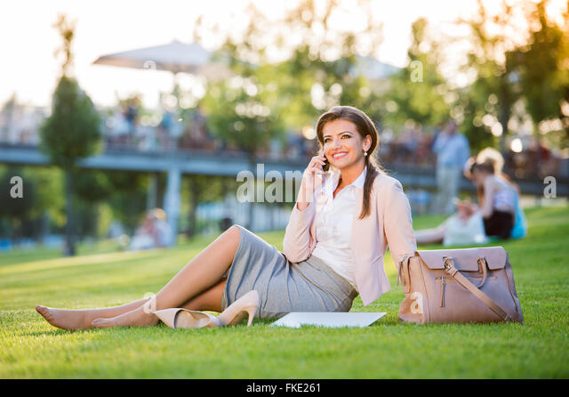 Businesswoman sitting in park, making a phone call, sunny day - Stock Image
