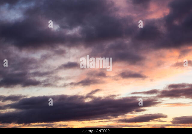 Colourful cloudscape at daybreak with purple, pink and yellow colours dominant - Stock Image